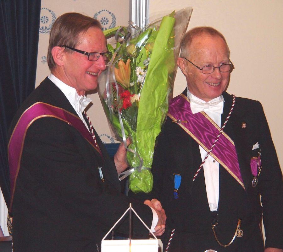 Den avtroppende Ordf.br. Rolf Schjem (t.h.) og påtroppende Jan Holt er venner og kamerater gjennom mange år, både i loge og på arbeidssted. Her utveksler de blomster, takk og lykkeønskninger.